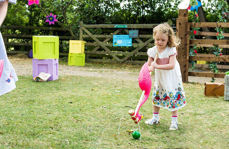 A girl playing croquet