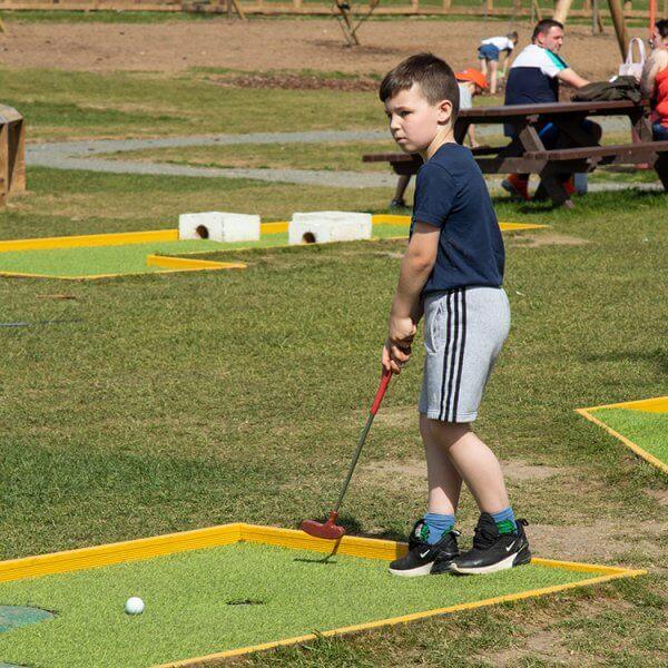 A boy playing crazy golf