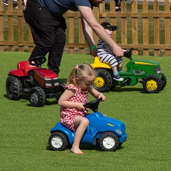 Kids playing on toy tractors
