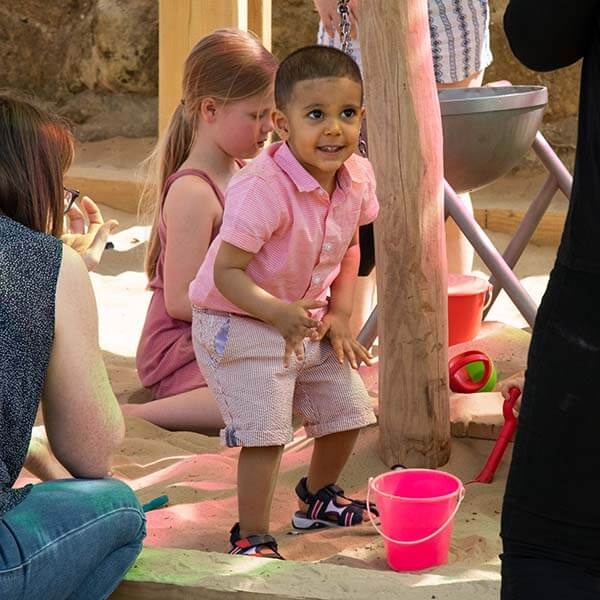 A child playing in the sand pit